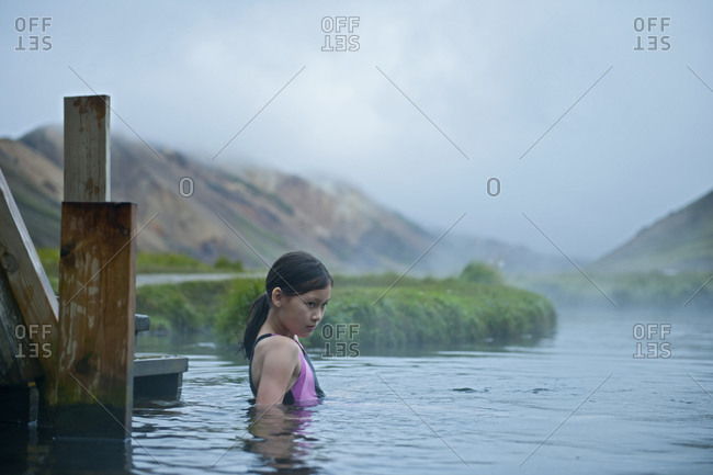 girl carefully taking a bath at geothermal hot spring in Iceland