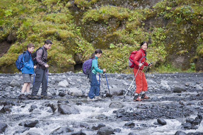 mother leading her children through canyon in Iceland
