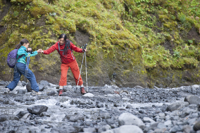 Mother helping her daughter jumping over river in Iceland