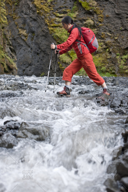 Woman hiking through canyon in Iceland with hiking poles
