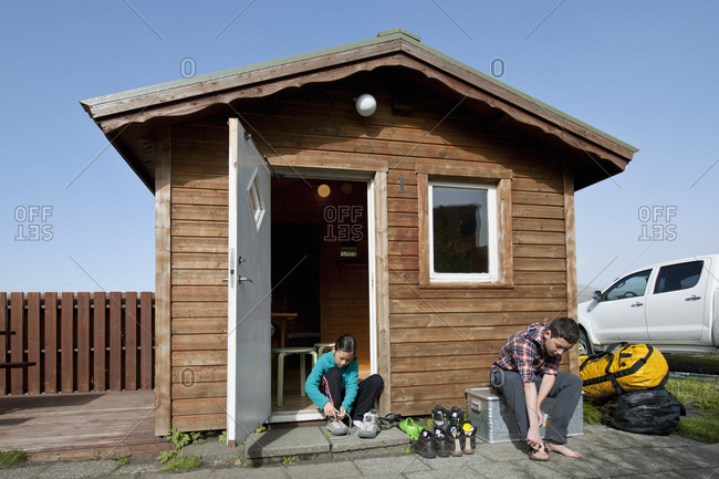 children are getting ready in front of wooden cottage in Iceland