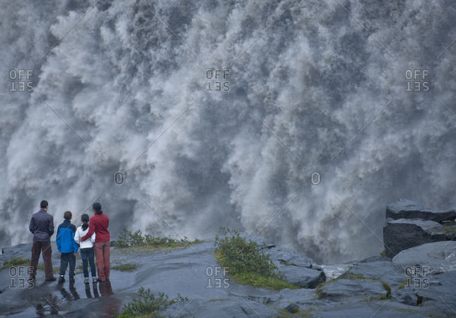 Family standing at the edge of the mighty waterfall Dettifoss