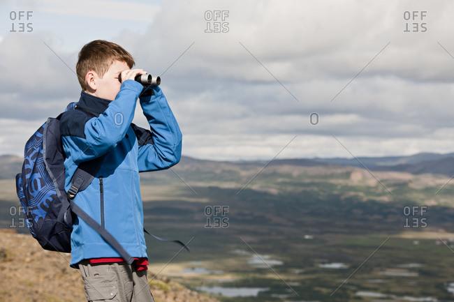 boy surveying the landscape at lake Myvatn with his binoculars