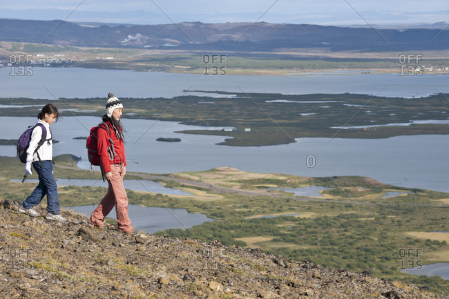 Mother and daughter ascending from mountain at Lake Myvatn