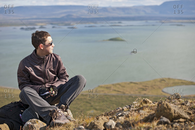 teenage boy resting on top of mountain above Lake Myvatn in Iceland