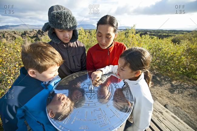Family checking compass rose at Lake Myvatn