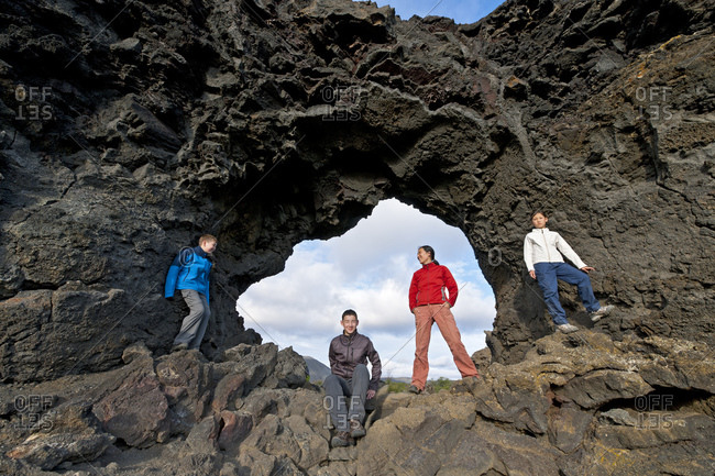 Family is posing at natural stone arch at Lake Myvatn in Iceland