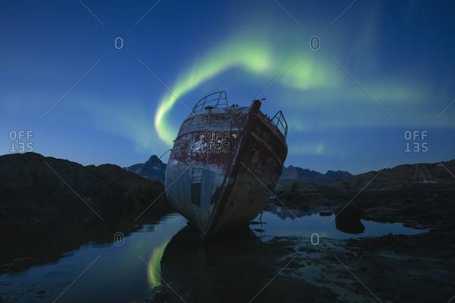 Northern Lights - Aurora Borealis in sky over boat wreckage, Tasiilaq, Greenland