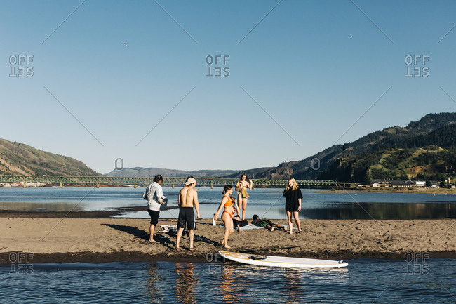 A group of people enjoy the sand spit in the Columbia River.