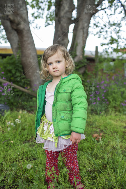 A portrait of a young girl wearing a green jacket in the backyard.