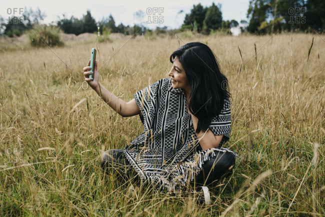 Portrait of a cute hispanic woman in the park making a selfie