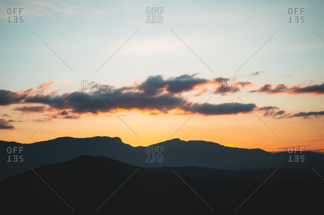 Silhouette of mountain range with beautiful clouds in the sky during sunset