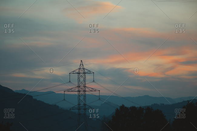 Electricity pylon with beautiful mountain layers and orange clouds in the background