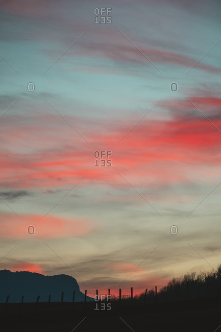 Silhouette of a fence with a mountain in the background during a beautiful sunset with pink clouds