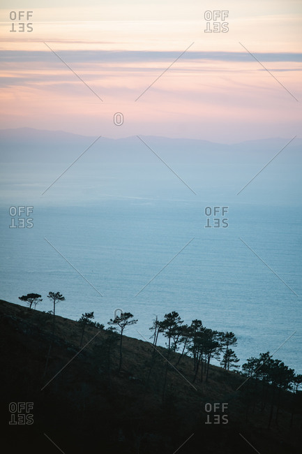 Silhouettes of trees on a steep hill next to the coast of Jaizkibel