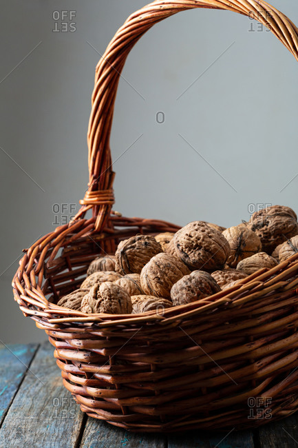 Close up of full basket of walnuts on wooden table