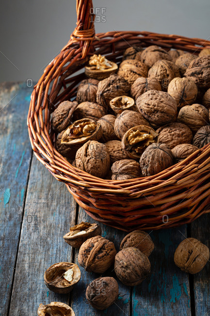 Basket overflowing with whole and cracked walnuts