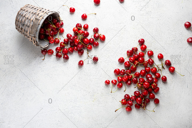 Overhead view of cherries out of bucket on light surface