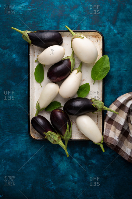 Overhead view of white and purple eggplants on tray