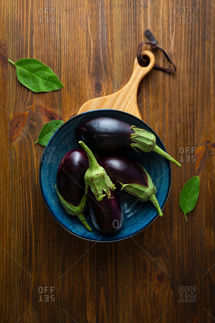 Overhead view of eggplants in bowl on rustic table