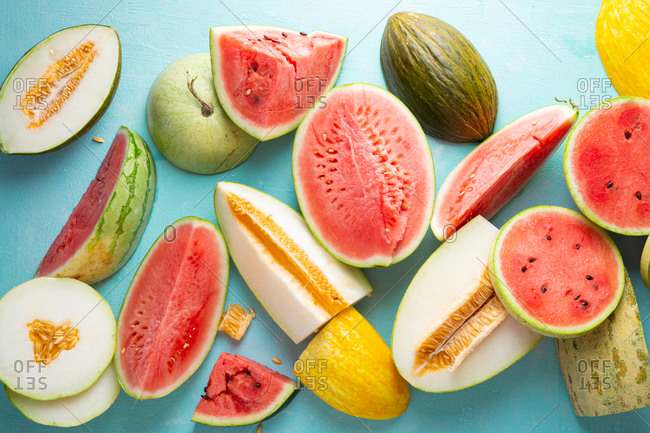 Melons and watermelon slices on light blue surface