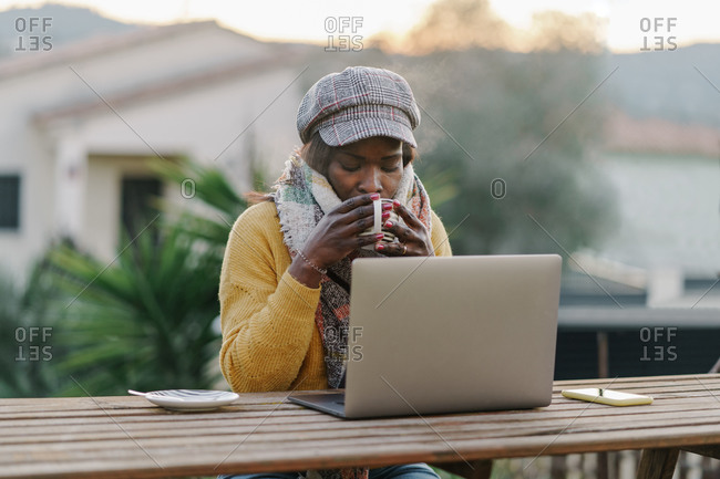 Black woman with hat and scarf sipping hot drink while sitting at table with laptop during break in remote work in yard