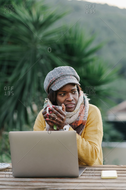 Stylish African American woman with mug of hot beverage sitting at table and looking away while working in yard