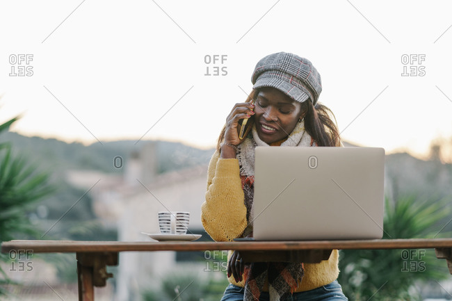 Black woman in trendy clothes smiling and answering phone call while sitting at table with laptop and working in yard