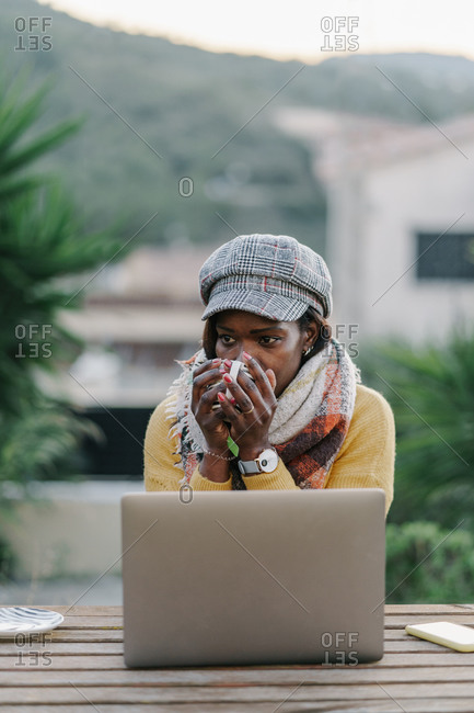 African American woman with scarf and hat and drinking hot beverage sitting at table in winter