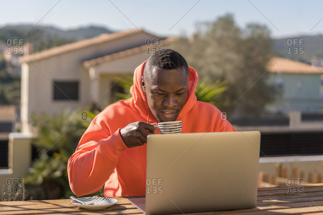 Young black man in red hoodie drinking hot beverage and browsing data on laptop while sitting at table and working on remote project in yard
