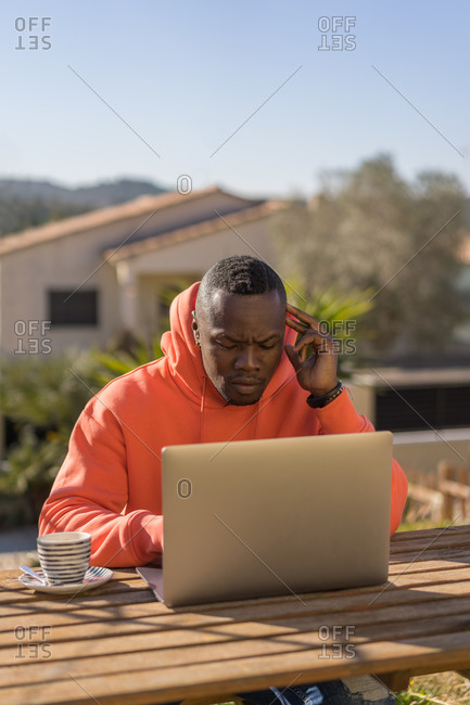 Young black man in red hoodie browsing data on laptop while sitting at table and working on remote project in yard
