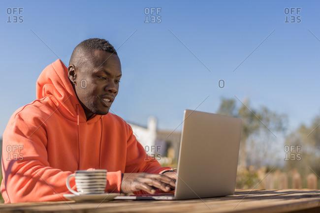 African American guy in orange hoodie with cup using laptop in yard