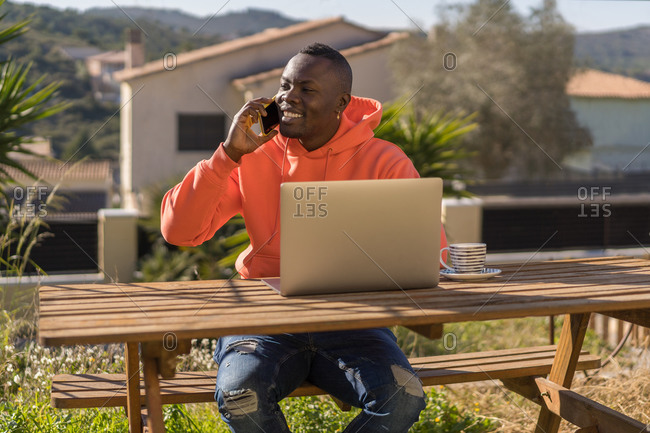 African American guy in casual clothes smiling and answering phone call while sitting at table in yard and using laptop for work