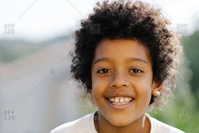 Portrait of smiling afro boy in white t-shirt in the garden