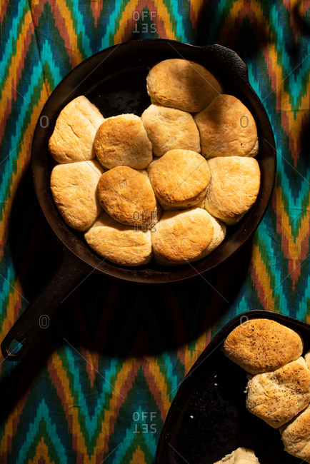 Cast iron skillet of biscuits on colorful background in dappled light