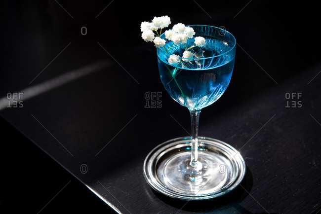 Blue curacao cocktail garnished with white flowers