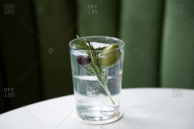 Clear cocktail garnished with rosemary and olives