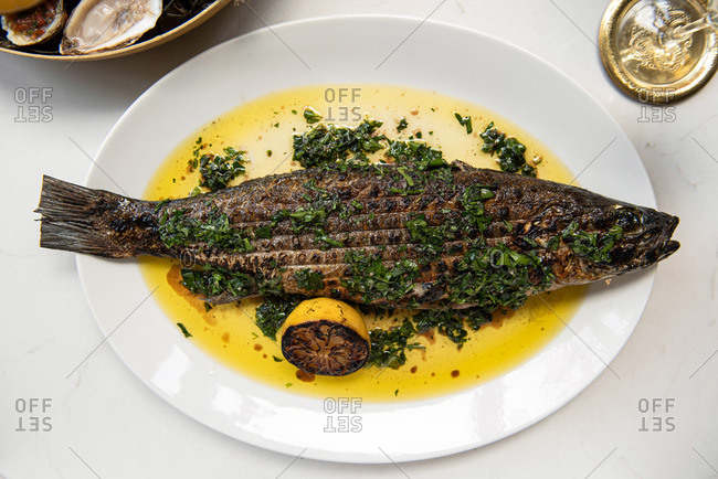 Whole grilled turbot fish on a white platter with lemon and herbs