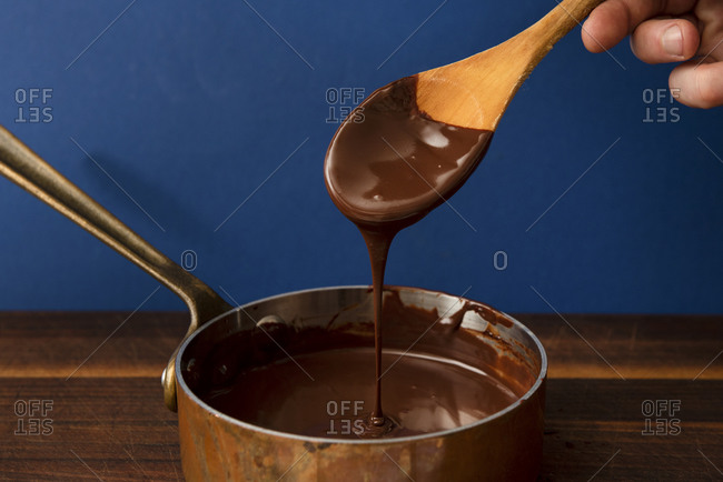 Hand holding a wooden spoon with melted chocolate ganache dripping into pot