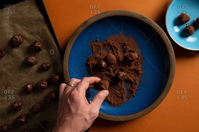 Overhead view of a baker rolling truffles in cocoa powder for chocolate truffles
