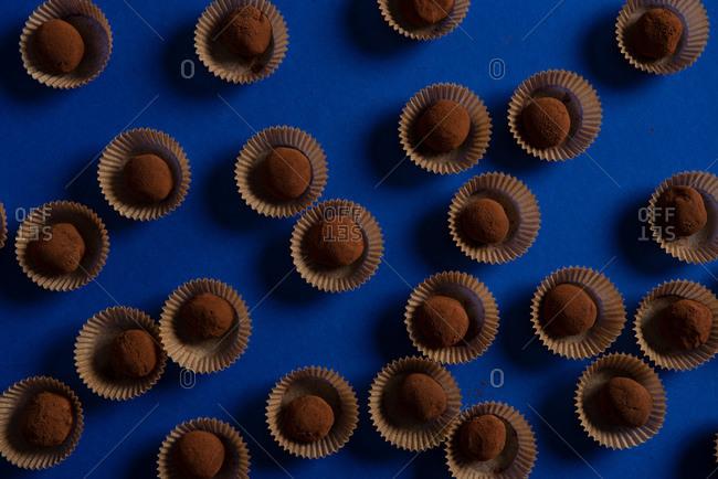 Many chocolate truffles on blue background