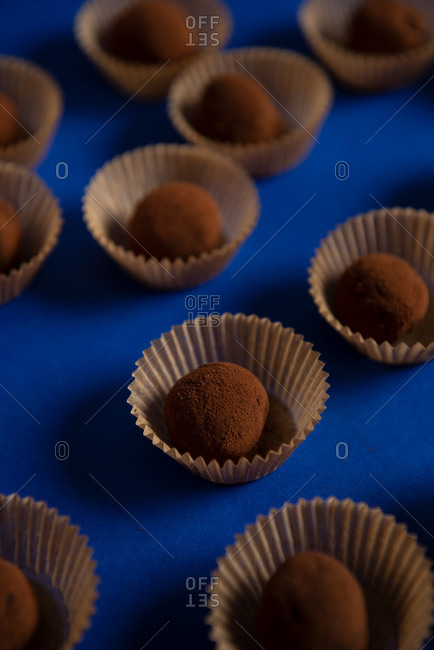 Close up of many chocolate truffles on blue background