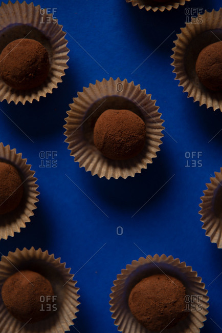 Top view of many chocolate truffles on blue background
