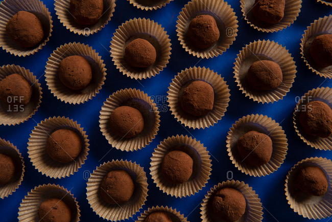Overhead view of many chocolate truffles on blue background