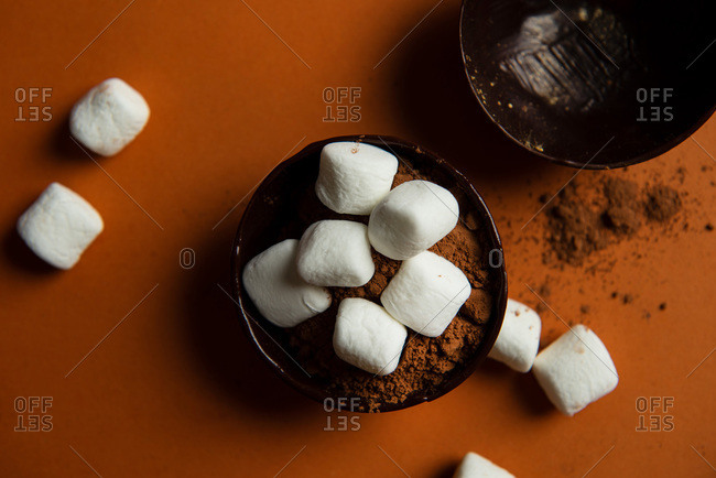 Overhead view of partially filled chocolate shells for hot chocolate bombs on orange background