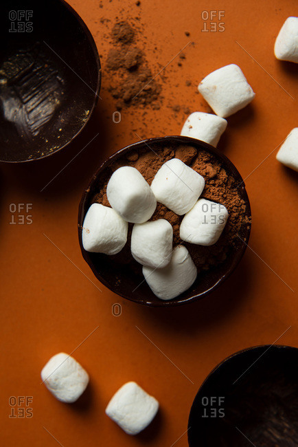 Partially filled chocolate shells for hot chocolate bombs on orange background