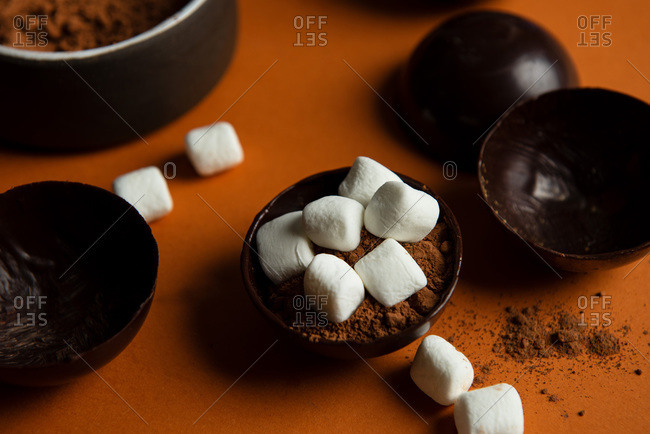 Top view of partially filled chocolate shells for hot chocolate bombs on orange background