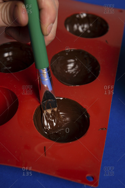 Baker painting a silicone mold with chocolate for hot chocolate bombs