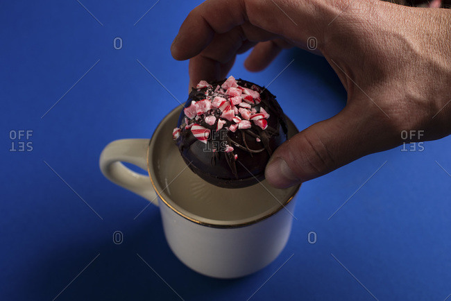 Hot chocolate bomb being placed into mug of hot milk