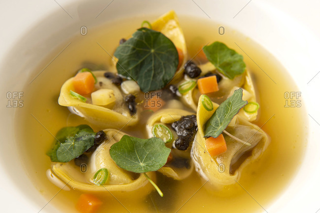 Close up of tortellini pasta in broth with diced veggies